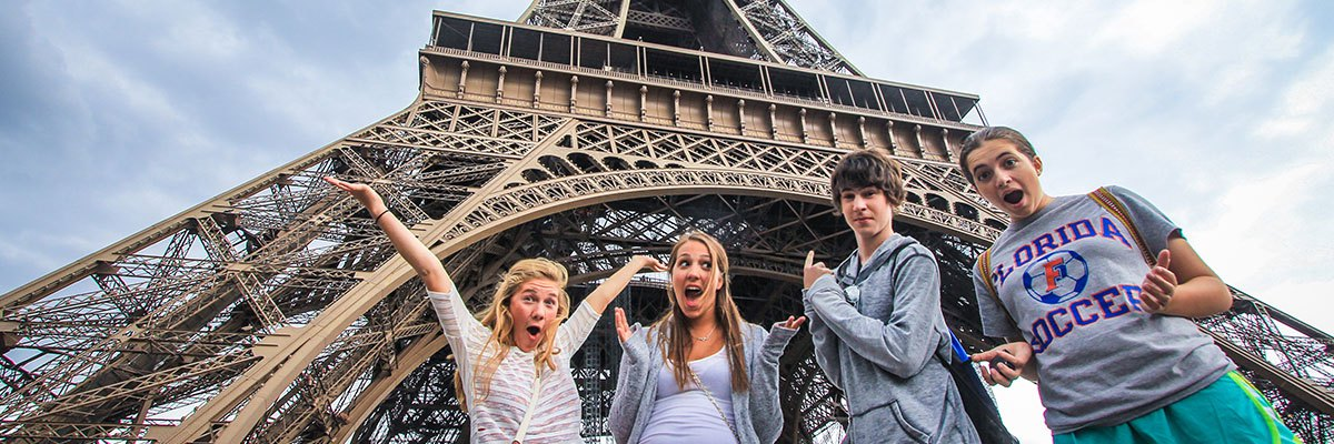 Teenage travelers visit Eiffel Tower during summer youth travel program in Paris