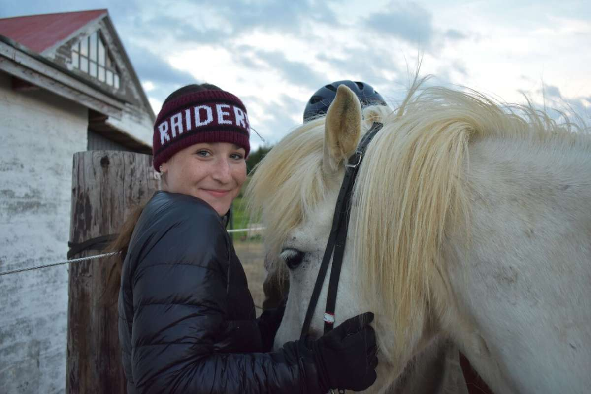 Teen traveler with Icelandic horse during summer youth adventure travel program