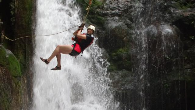 Teens zip-line across a waterfall on their summer adventure program in Costa Rica.