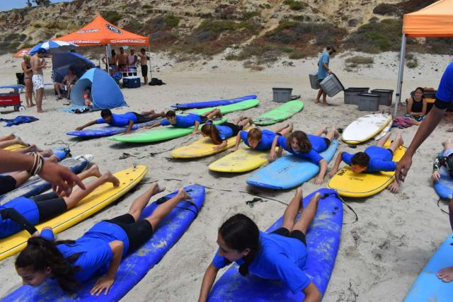 A group of students learns how to surf on their summer teen tour of California.
