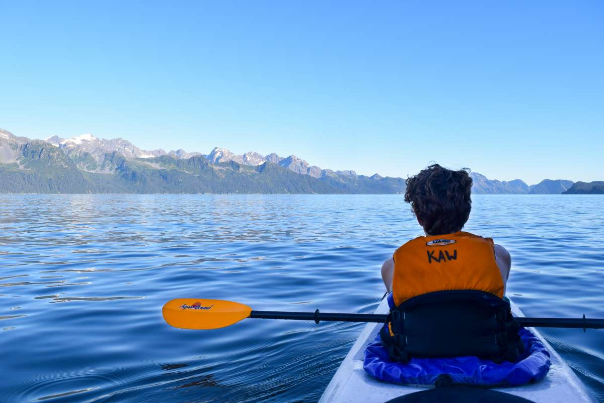 Teenage traveler kayaking Alaska on summer travel program