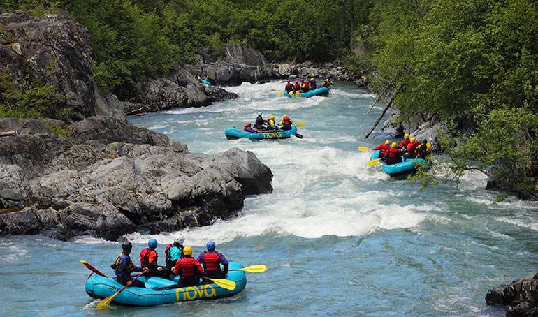 Teen travelers whitewater rafting in Alaska on summer adventure and service program.