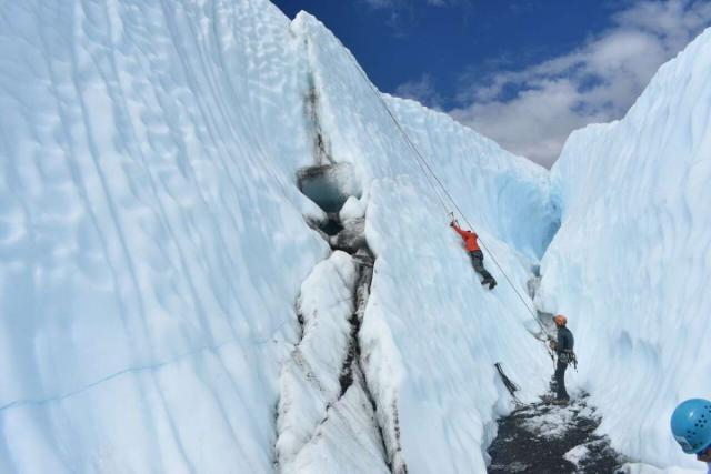 Teen traveler ice climbing in Alaska on summer travel program