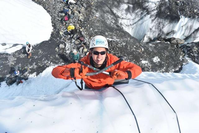 Teen traveler ice climbing on Alaska summer travel program