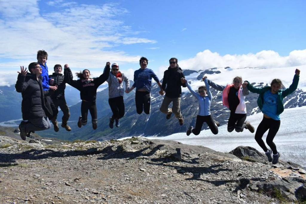 Group of happy teens jumping in Alaska on summer travel tour