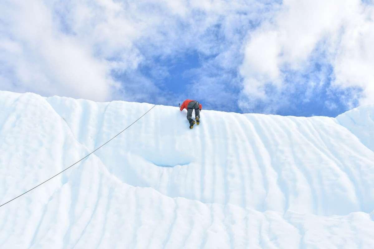 Teen traveler ice climbing in Alaska on summer program