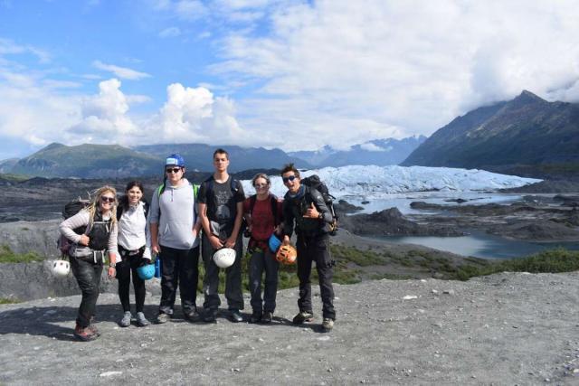 Group of happy teens hiking Alaska wilderness on travel program