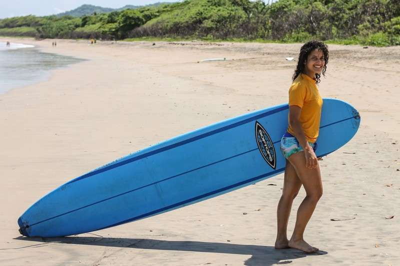 Teen brings her surfboard onto the beach on her summer adventure tour of Costa Rica.