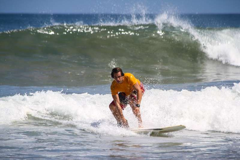 Teen boy surfs the waves of Costa Rica on a summer adventure tour.