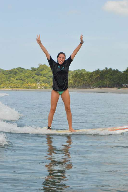 Teen learns how to surf on summer adventure program in Costa Rica.