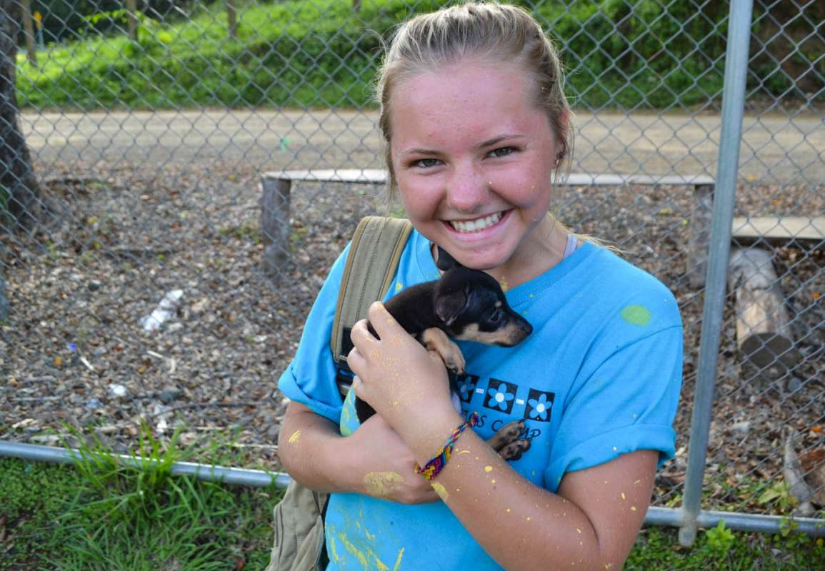 Teen poses with puppy on Costa Rica animal rescue program.