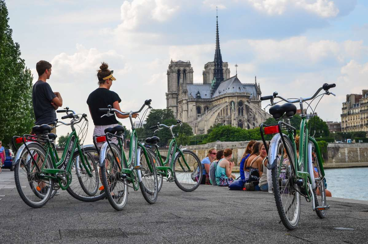 Teen travelers biking by Notre Dame on summer travel program