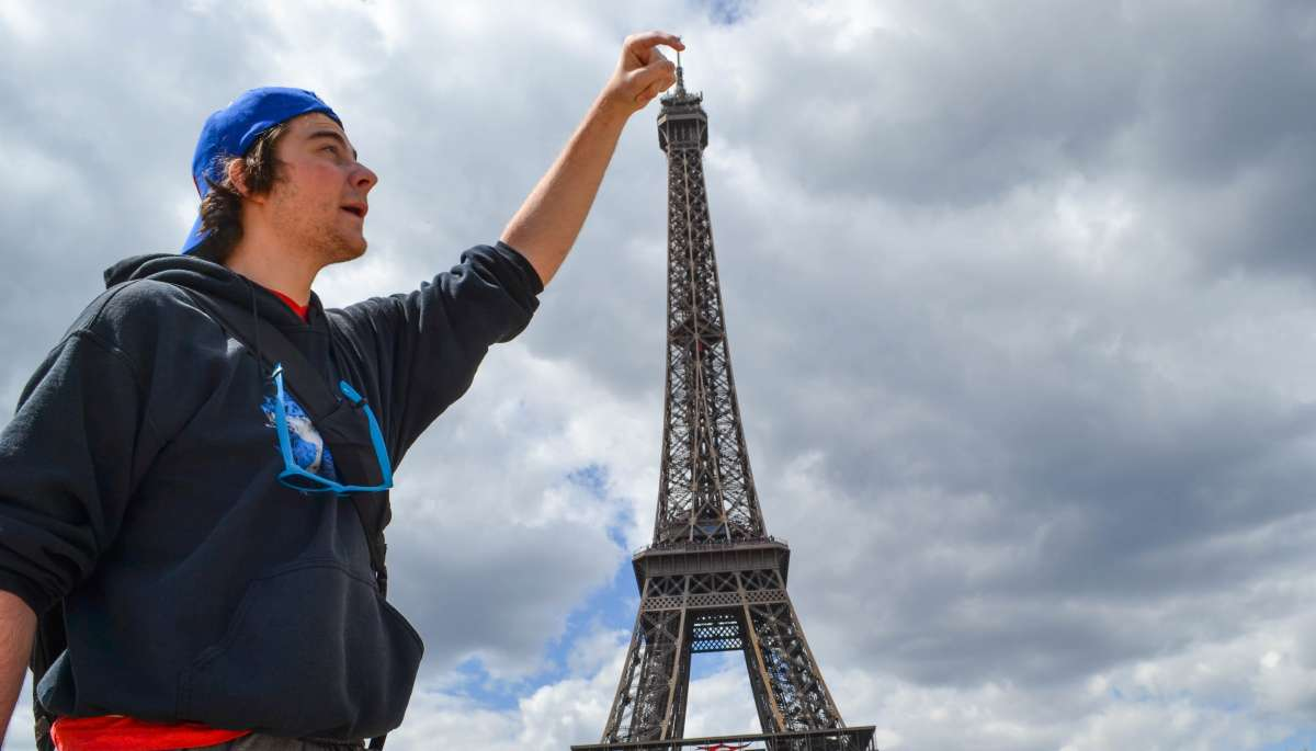 Teenage traveler with Eiffel Tower during summer youth travel program in Paris