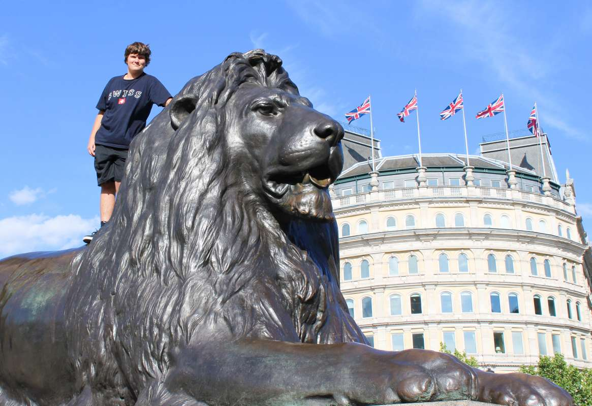Teenage traveler with lion statue in Trafalgar Square during summer youth travel program in London