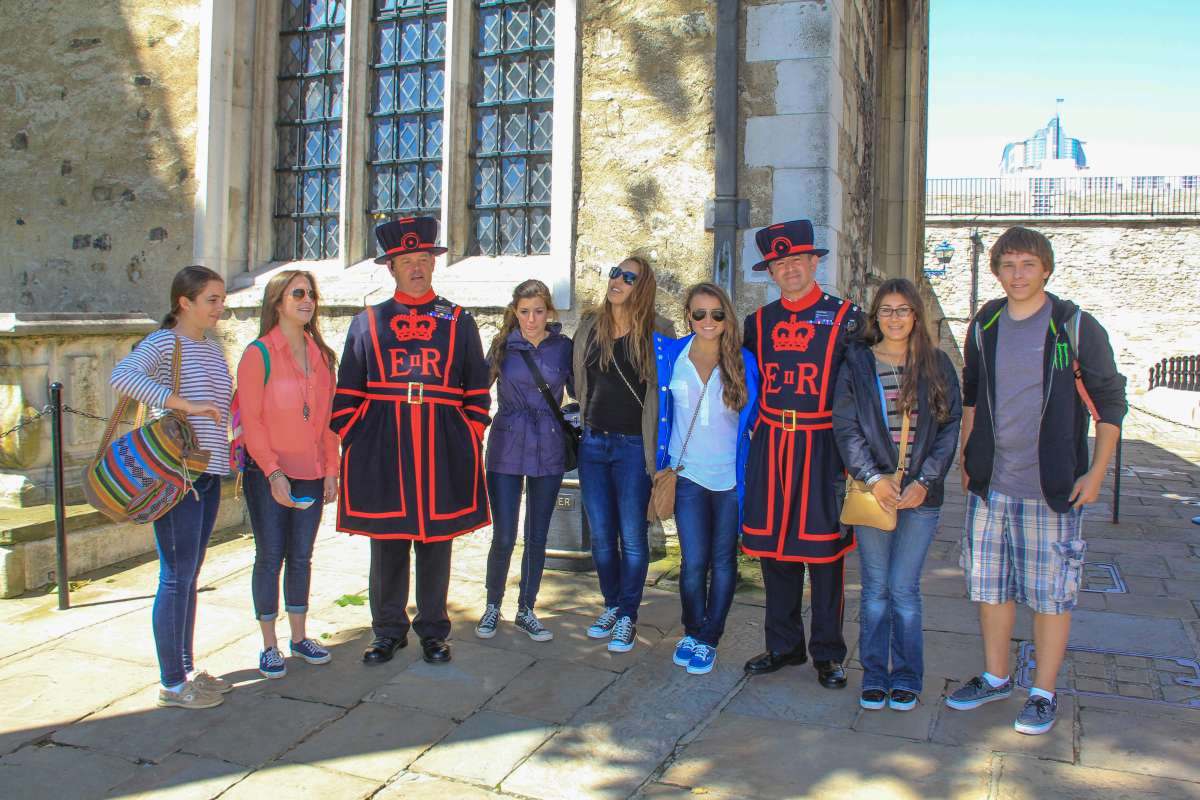 Younger travelers with Beefeater guards at Tower of London on summer student travel program