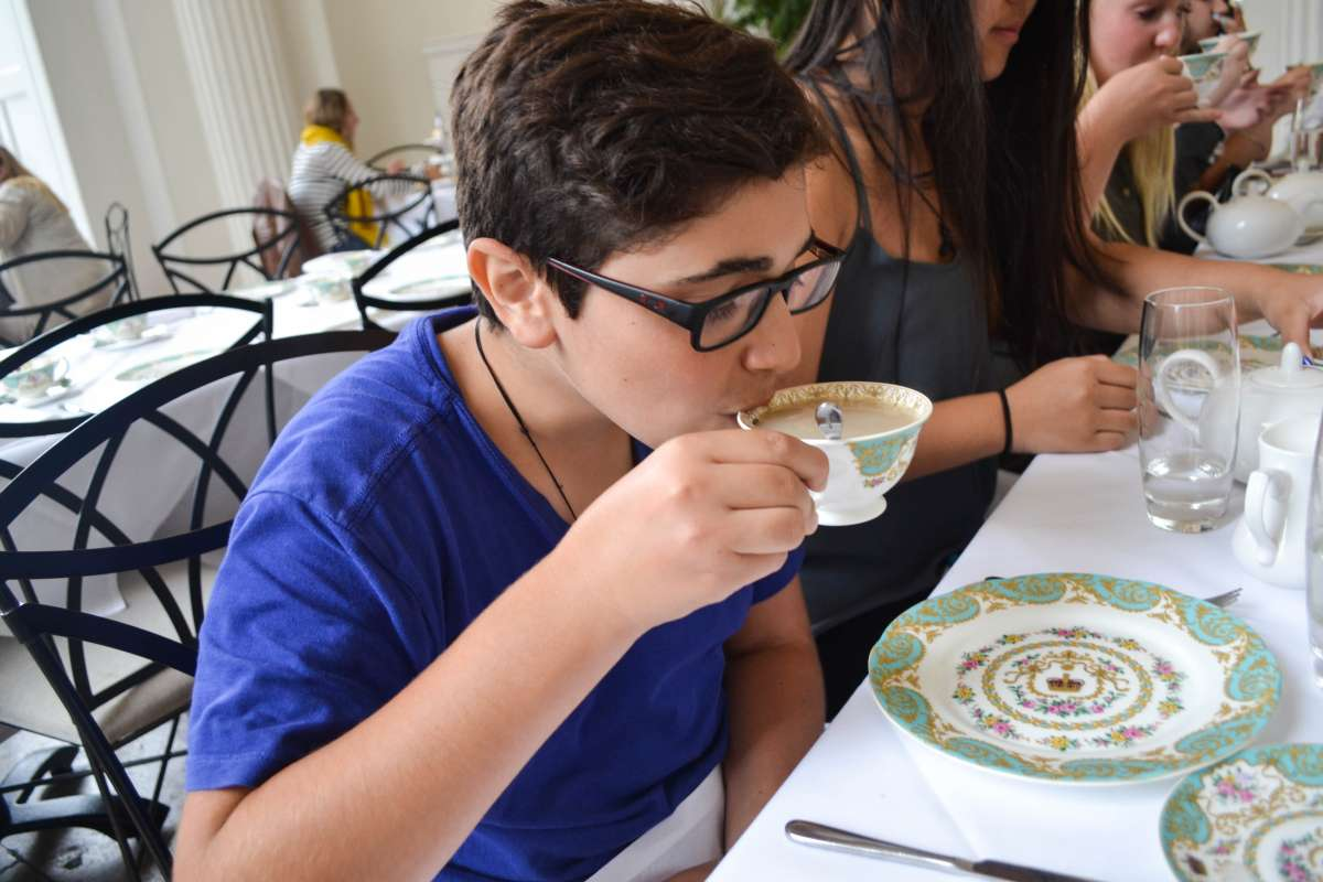 Teen traveler drinks afternoon tea in England on summer travel program