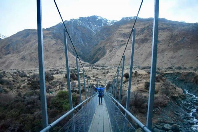 Teenage traveler crosses bridge during summer youth travel program in New Zealand