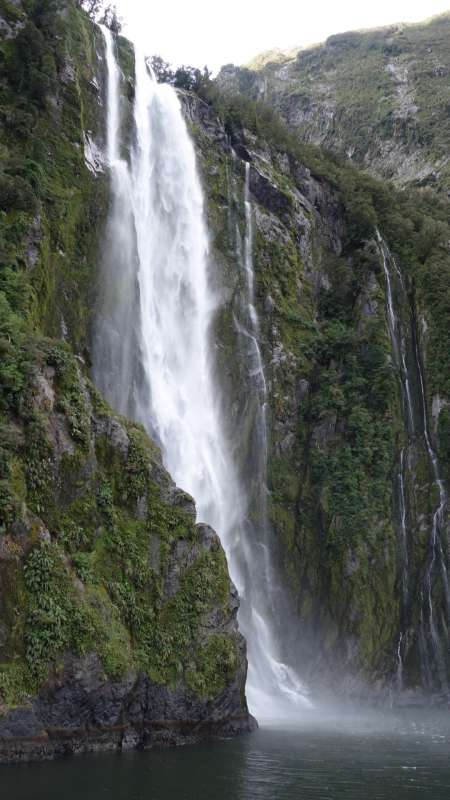 Scenic waterfall seen by teenage travelers during summer youth travel program in New Zealand