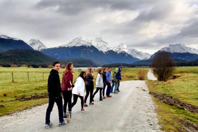 Happy teenage travelers walk down road with mountains during summer youth travel program in New Zealand