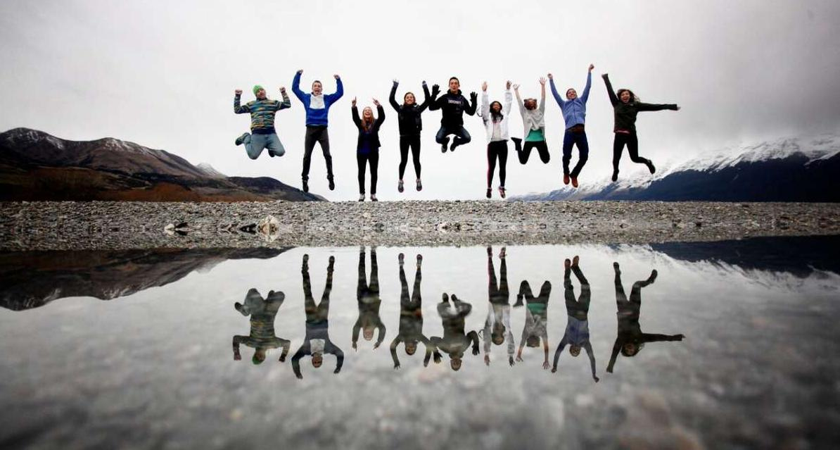 Group of happy teens jumping with a reflection in Australia and New Zealand on a summer travel tour