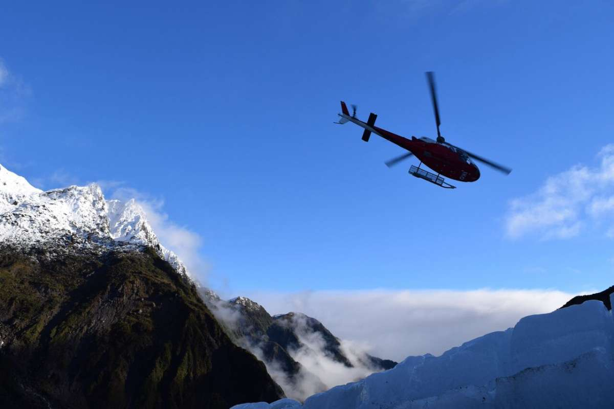 Teenage travelers take helicopter tour during summer youth travel program in New Zealand