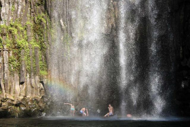 High school travelers swim underneath waterfalls Down Under on a teen tour to Australia and New Zealand.