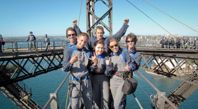 Group of happy teens climbing the Sydney bridge on a summer travel tour.