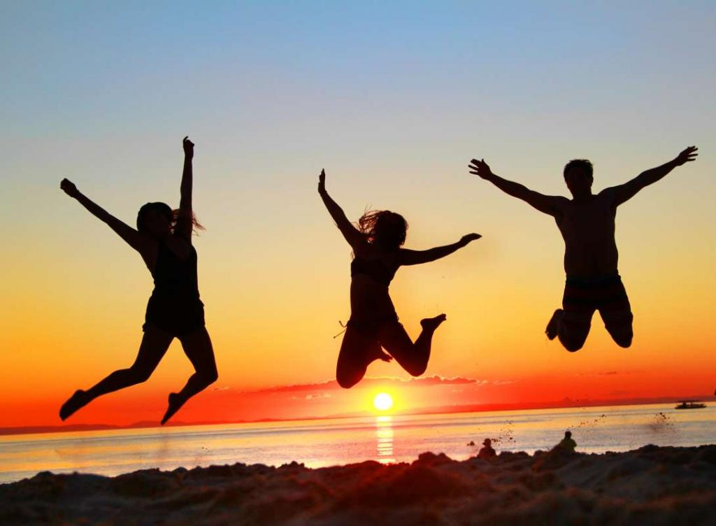 Group of happy teens jumping at sunset on a summer travel tour