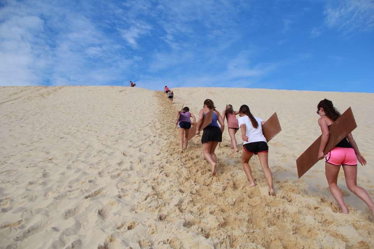 Teen travelers hike up a sand dune in Australia on a summer teen tour.