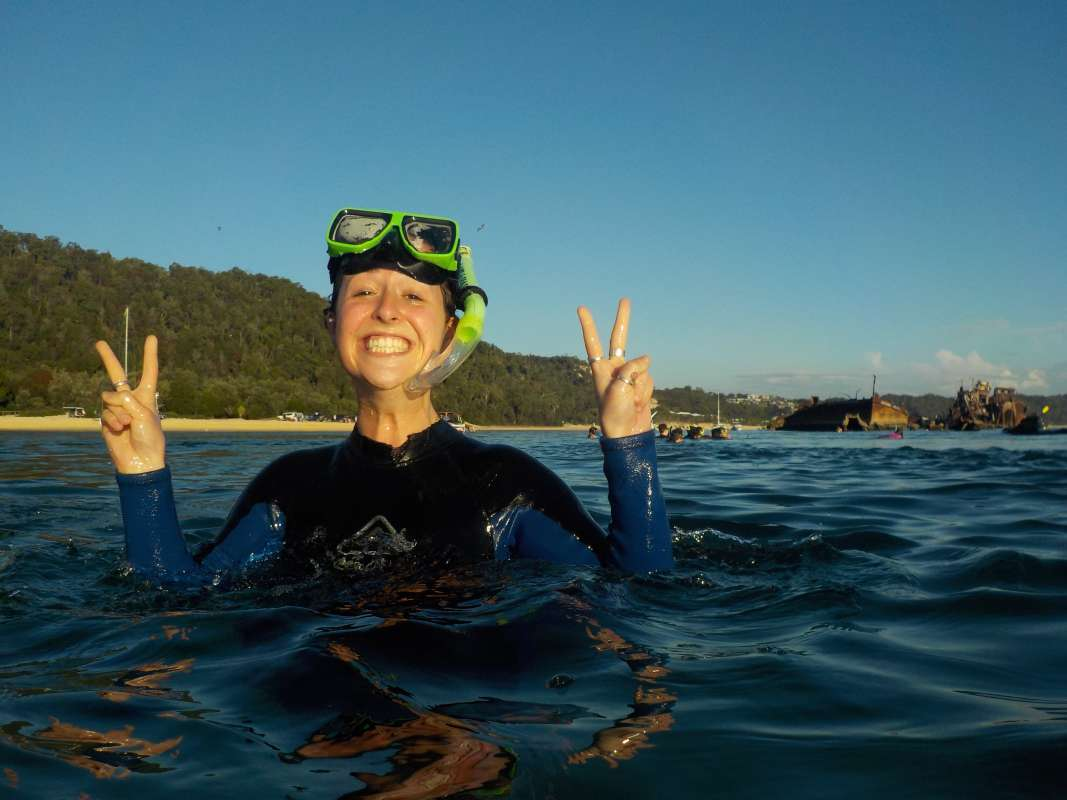 Teenage traveler dives into Australia's ocean on a summer teen tour.