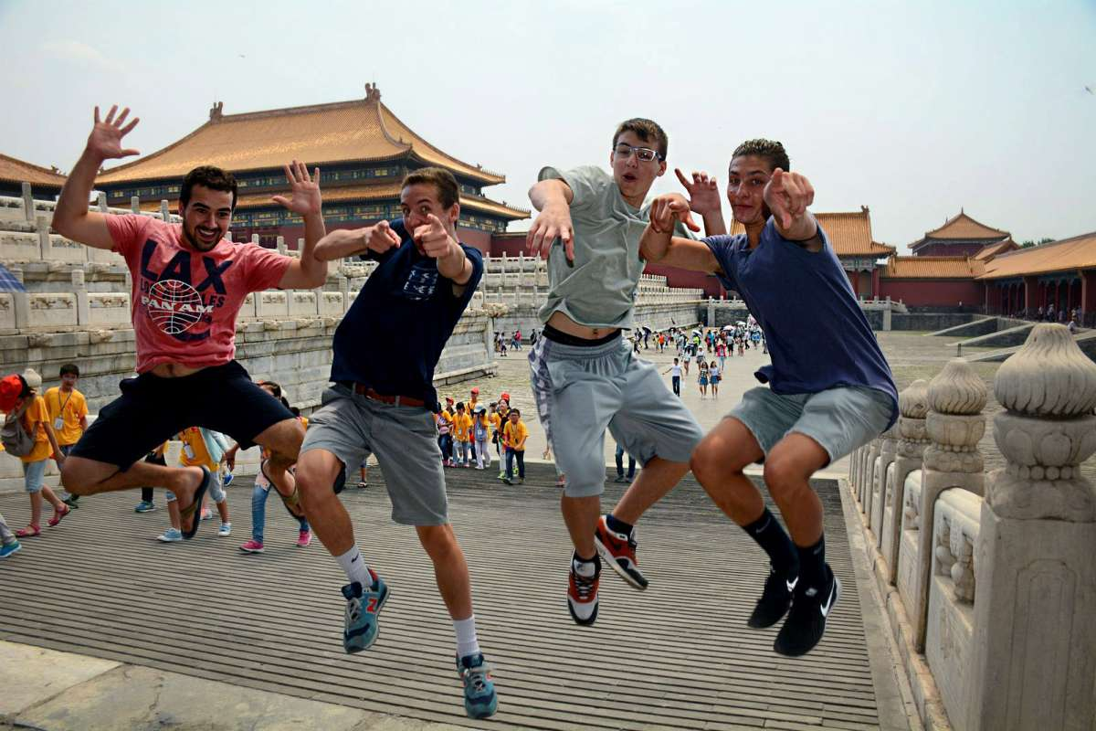A group of students jump for joy on their teen tour of China.