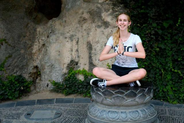 A girl meditates in China on her summer teen tour.