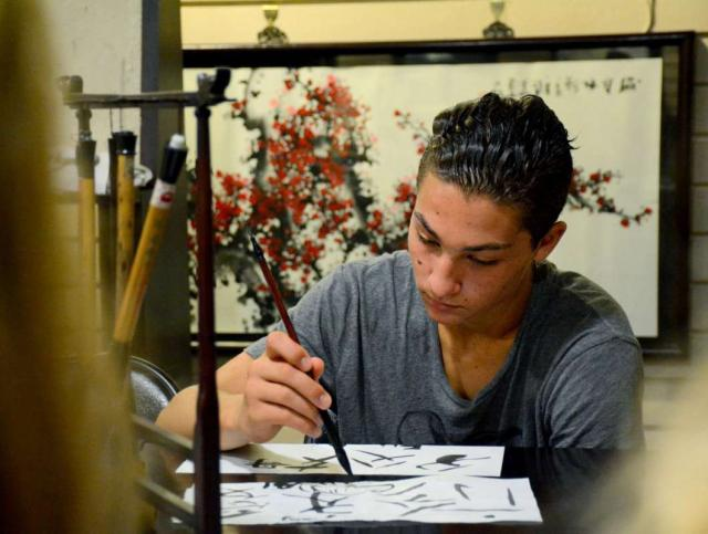 A boy practices Chinese calligraphy on his teen tour of China.