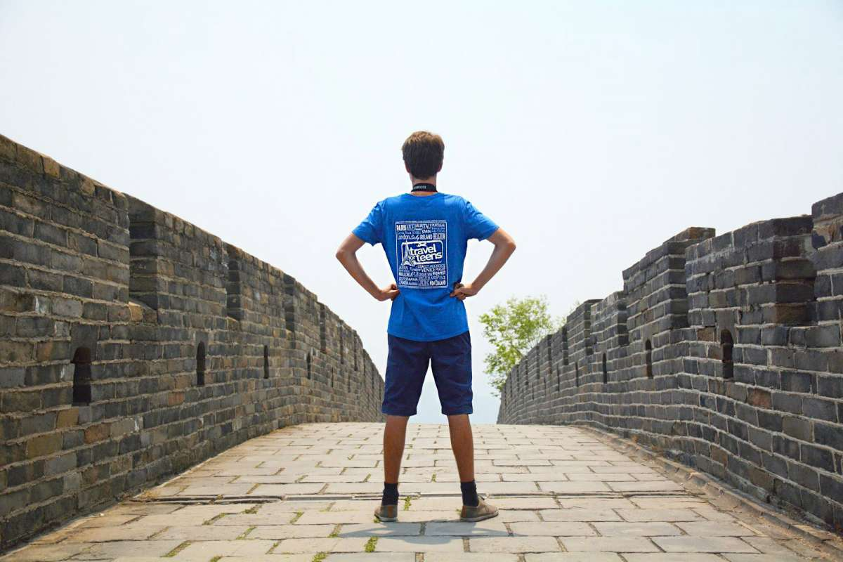 Student poses on the Great Wall of China on their summer teen tour.