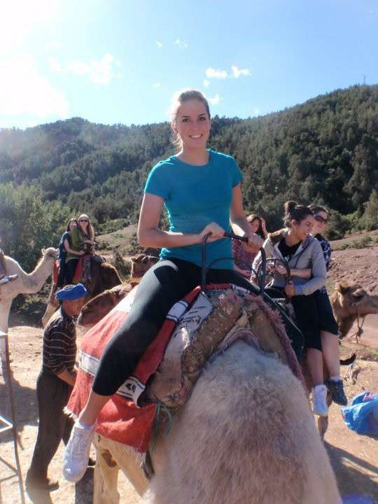 Teenage traveler rides camel in Atlas Mountains of Morocco during summer teen adventure travel program