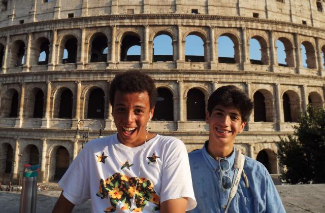 Teens smile in front of the Colosseum on their summer camp program to Italy.