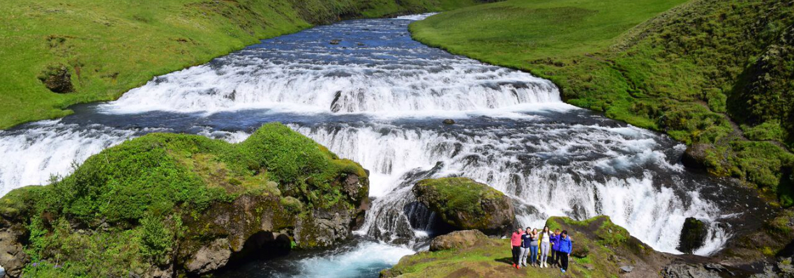 Teens with Iceland waterfall on summer youth adventure travel program