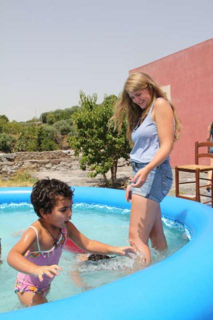 Teenage traveler plays with kids in pool during summer youth travel program in Sicily Italy