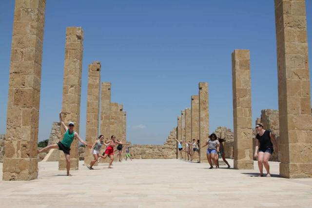 Happy teenage travelers explore archaeological ruins in Sicily Italy during summer youth travel program