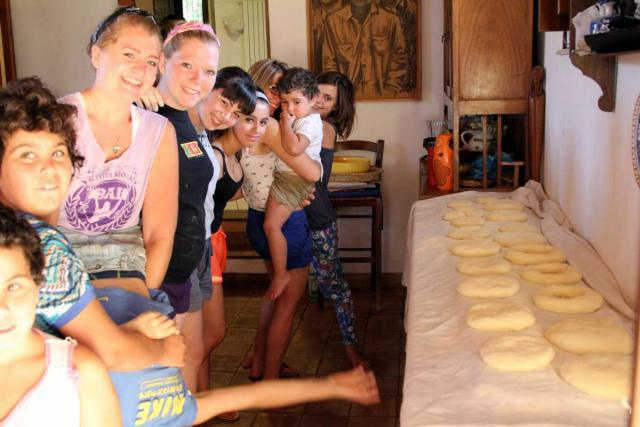 Teenage travelers with Italian children at cooking class during summer youth travel program in Sicily