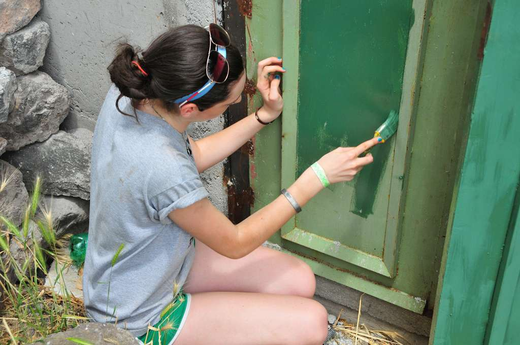 Teenage traveler paints and volunteers community service during summer youth travel program in Sicily Italy
