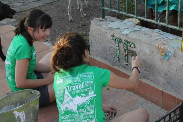 Teenage travelers volunteer to paint during summer youth travel program in Sicily Italy