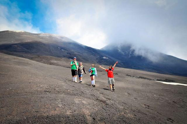 Teenage travelers climb Mount Etna on Sicily during summer youth travel program in Italy