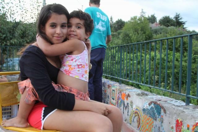 Teenage traveler hugs little Italian girl during summer youth travel program in Sicily Italy