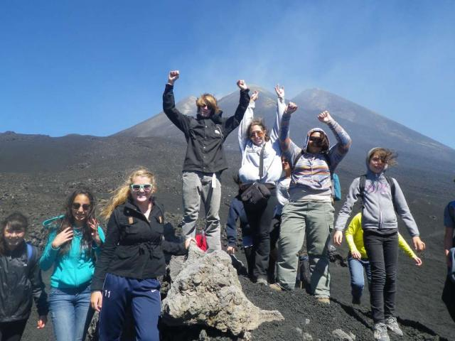 Happy teenage travelers climb Mount Etna during summer youth travel program in Sicily Italy