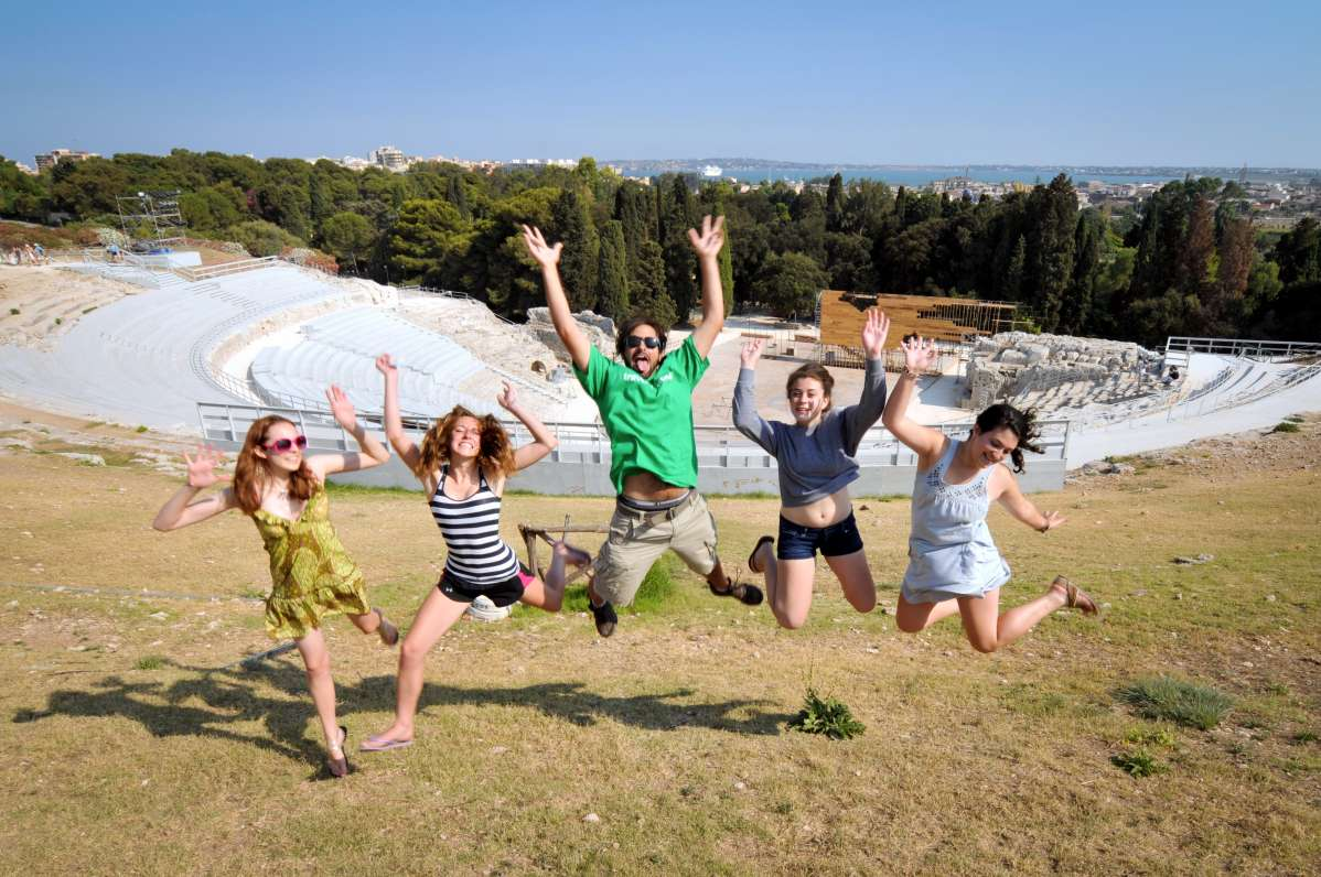 Happy teenage travelers visit ancient archaeological amphitheatre in Sicily during summer youth travel program in Italy