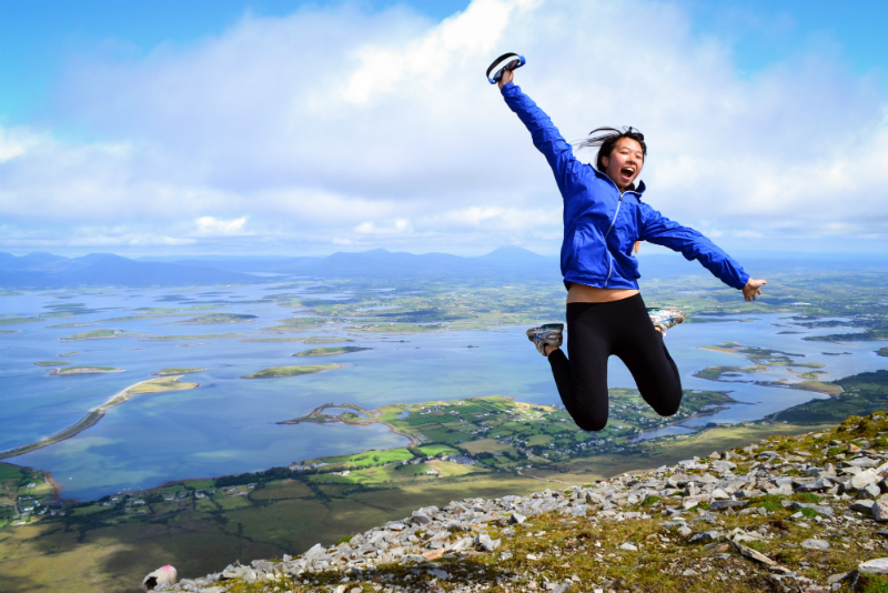 Happy teen jumps on Croagh Patrick during summer youth adventure travel program in Ireland