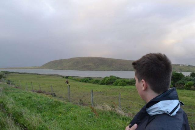 Teenage traveler walks in rolling green hills of Ireland on summer youth adventure travel program
