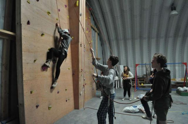 Teenage travelers climb walls in Ireland during summer teambuilding adventure travel program