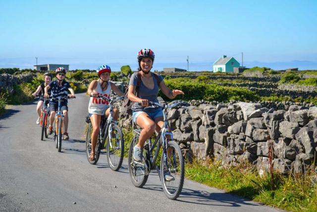 Teenage travelers bike through Aran Islands on summer youth adventure program in Ireland